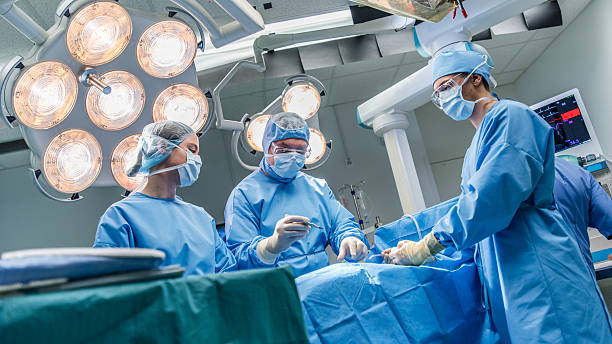 Surgeons in operating theatre Surgeons doing surgery in operating theatre. medical procedure stock pictures, royalty-free photos & images