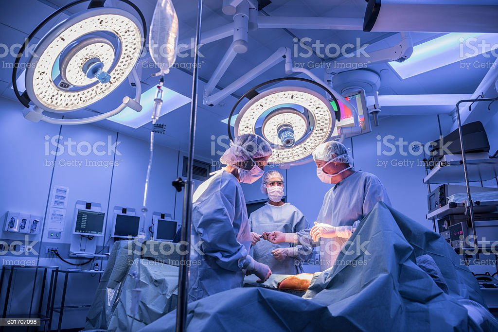 Surgeons operating on patient in operating theatre under lights stock photo