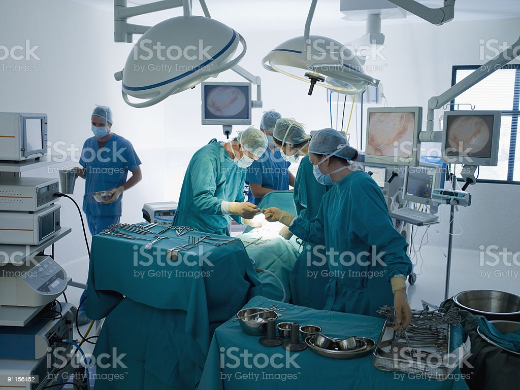 Surgeons performing operation in operating room stock photo