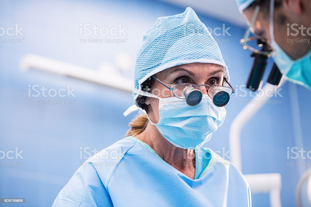 Surgeons performing operation in operation room stock photo