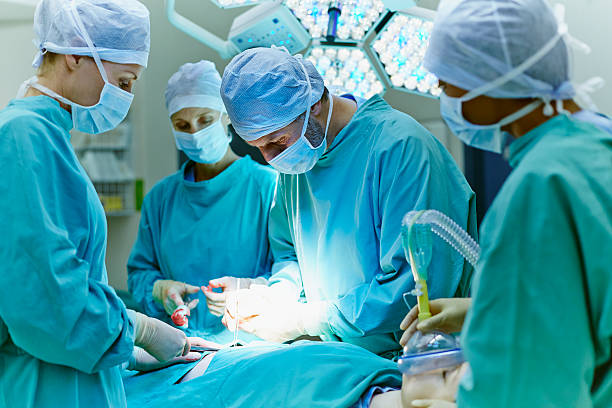surgeons performing surgery in operating room - surgeon стоковые фото и изображения