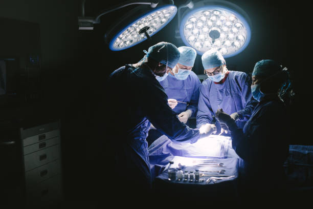 Surgeons performing surgical procedure in operating theatre Doctors during surgery on patient in hospital. Surgeons team working at the hospital performing surgical procedure in operating theatre. medical procedure stock pictures, royalty-free photos & images