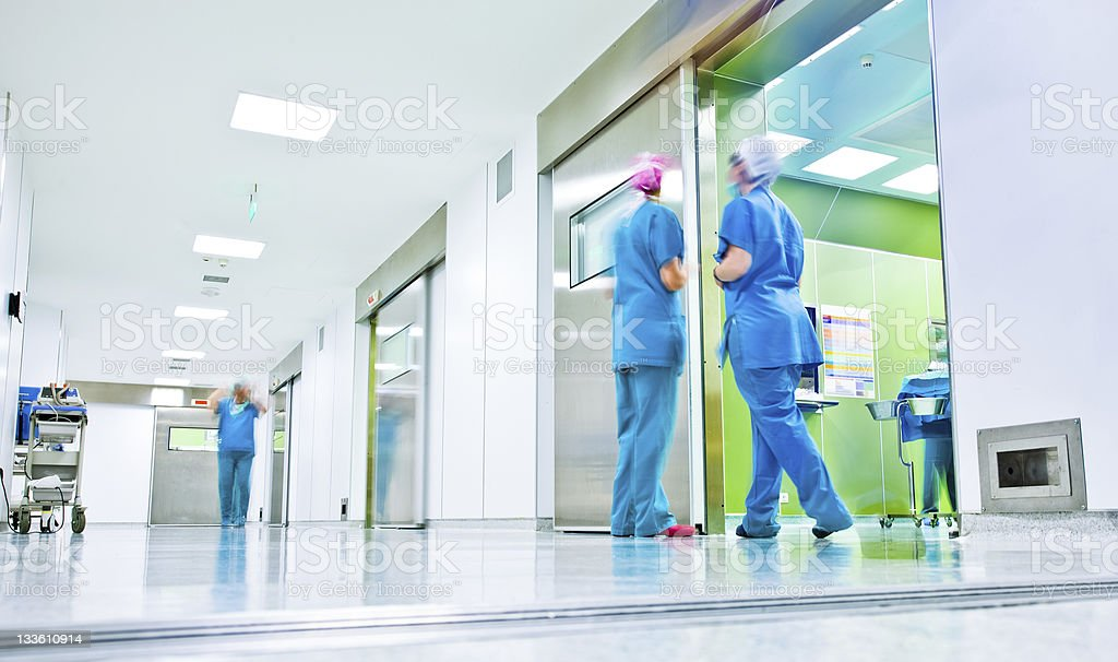 Surgeons talk in a hospital corridor blurred figures wearing medical uniforms in hospital surgery corridor Blurred Motion Stock Photo