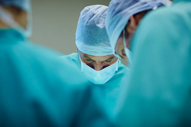 Surgeons working in operating room - foto de stock