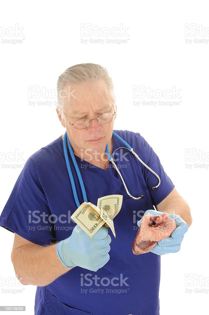 Surgeonwith fist full of money and a heart royalty-free stock photo