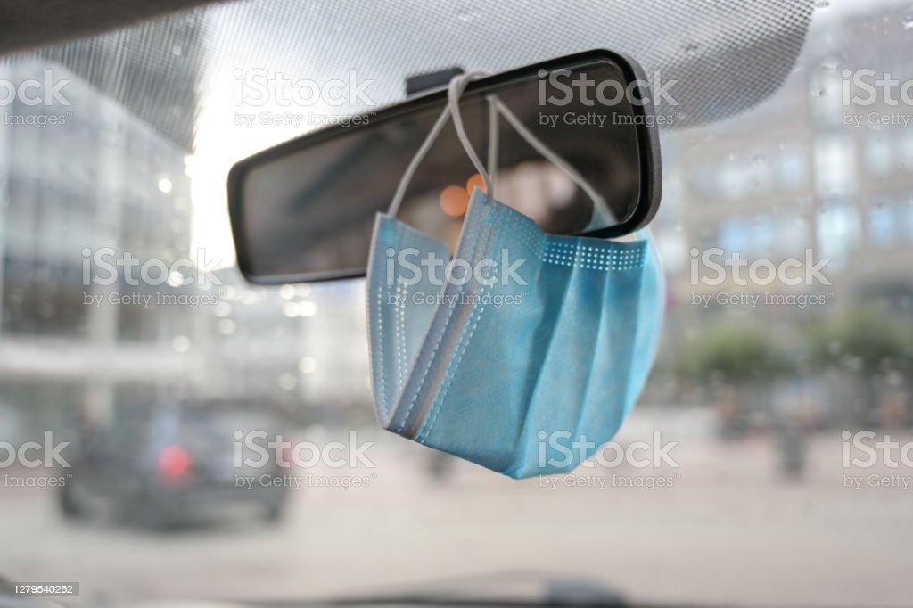 Chirurgisch gezichtsmasker als bescherming tegen covid-19 infectie hangt in een auto op de achteruitkijkspiegel tijdens het coronavirus pandemie, kopieerruimte - Royalty-free Apparatuur Stockfoto