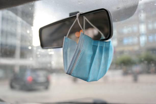chirurgisch gezichtsmasker als bescherming tegen covid-19 infectie hangt in een auto op de achteruitkijkspiegel tijdens het coronavirus pandemie, kopieerruimte - mirror mask stockfoto's en -beelden