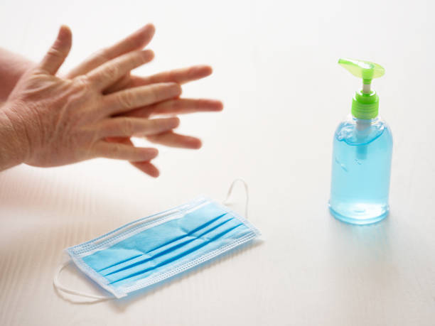 Surgical face mask next to a bottle of hand sanitizer, with someone cleaning their hands with the sanitizer, scene set on a white table background, selective focus with the focus being on the face mask in the foreground. stock photo