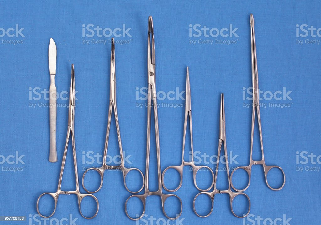surgical instruments and tools including scalpels, forceps and tweezers arranged on a table for a surgery stock photo