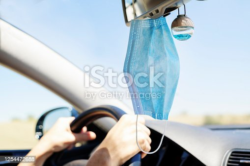 surgical mask hanging from the rear view mirror of a car selective focus