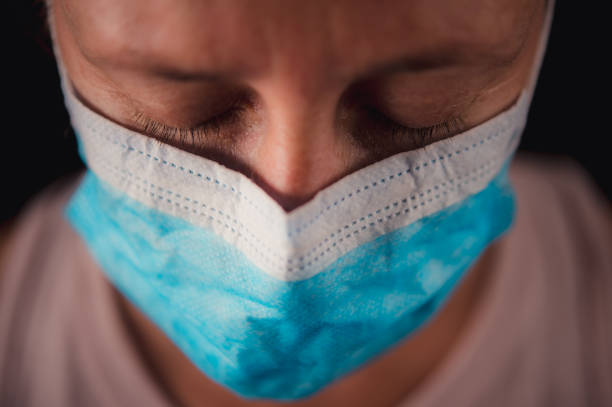 chirurgisch maskerportret van een droevige vrouw die neer met lopende scheur kijkt - tears corona stockfoto's en -beelden