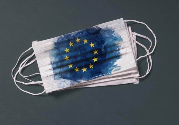 Surgical mask with European Union flag, Concept of global spread of Coronavirus Novel 2019-nCoV virus stock photo