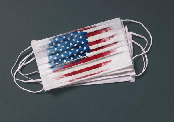 Surgical mask with USA flag, Concept of global spread of Coronavirus Novel 2019-nCoV virus stock photo