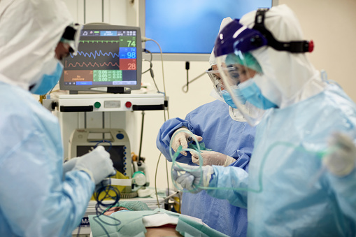 Doctors and nurses wearing surgical gowns over protective suits, eyewear, face shields, and masks as they prepare for surgical procedure.
