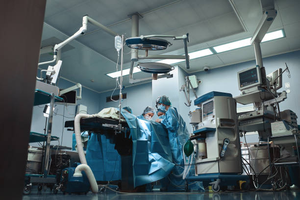 Surgical team operating on patient in theater in hospital stock photo