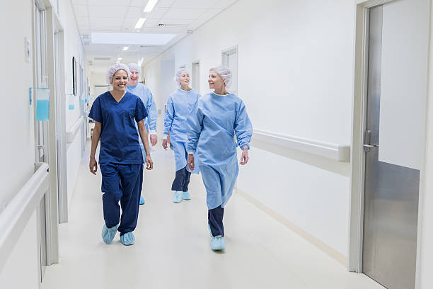 surgical team walking down hospital corridor, front view - australian nurses stock photos and pictures