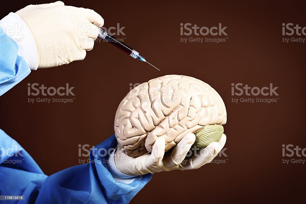 Surgically gloved hands inject model brain, Frankenstein style royalty-free stock photo