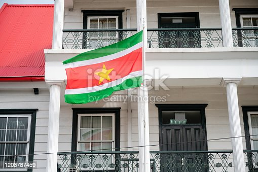 National flag of former dutch colony Suriname flying in front of a dutch-colonial style building in Paramaribo the capital city
