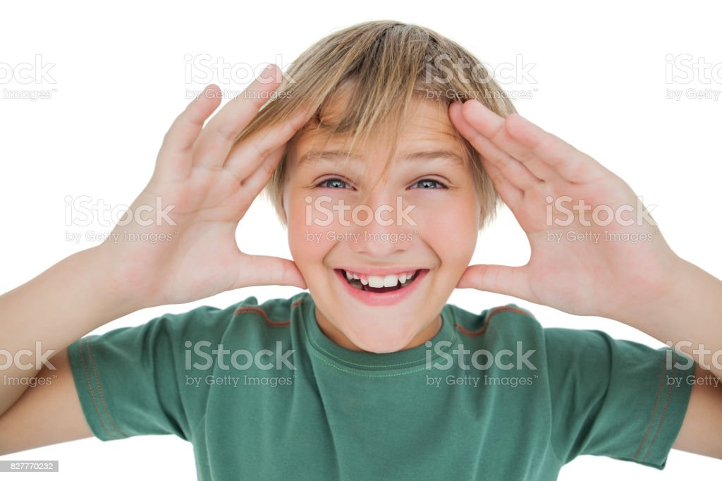 Surpised boy smiling with hands raised stock photo