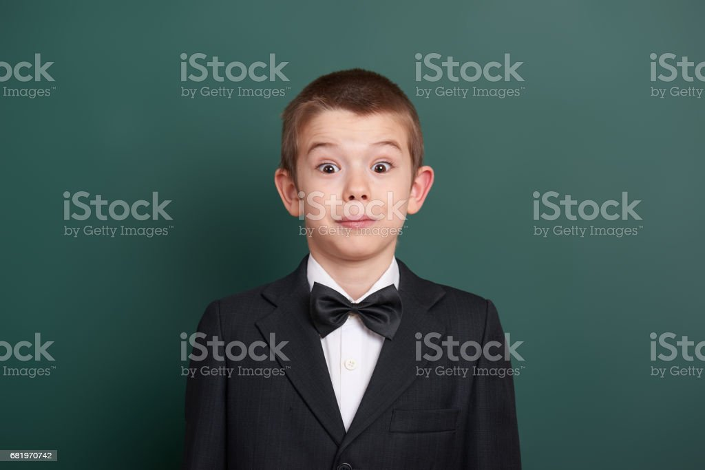 surpised school boy portrait near green blank chalkboard background, dressed in classic black suit, one pupil, education concept stock photo