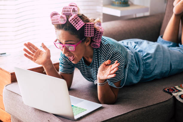 Surprise and excited happy woman at home looking laptop computer sitting on the sofa - beauty hair care fre female people - receiving news notification emails and happiness stock photo
