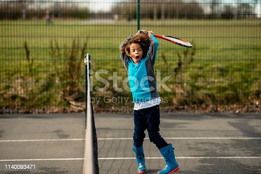A young boy playing tennis, holding the racket ready to swing.