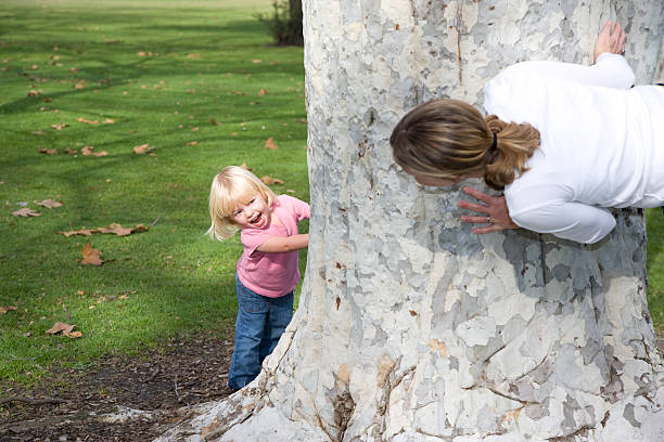 surprise behind tree. - mom spying stock photos and pictures