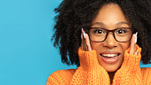 istock Surprise biracial woman in orange jumper surprise holding cheeks by hands. Mixed race girl wear glasses with clean fresh skin looking at camera, isolated on studio blue background. Black Friday, sale 1294114831