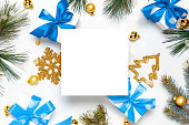 istock Surprise box. White gifts with blue bow, golden balls and Christmas tree in xmas decoration on white background for greeting card. Flat lay, top view, copy space. 1285617477