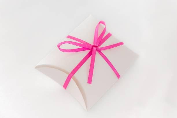 niedliche wertvolle luxus überraschungsgeschenk mit schleife am weißen tisch - geschenk zur taufe stock-fotos und bilder