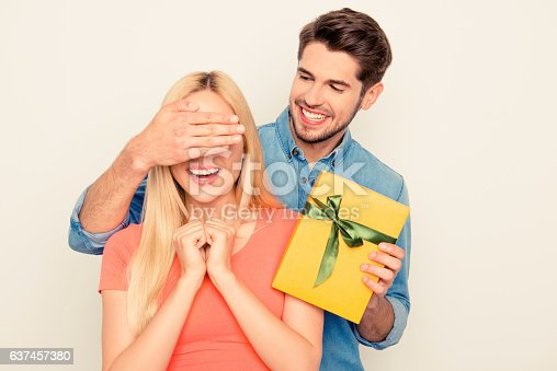 1136623274istockphoto Surprise! Guy closing eyes of his girlfriend and holding present 637457380