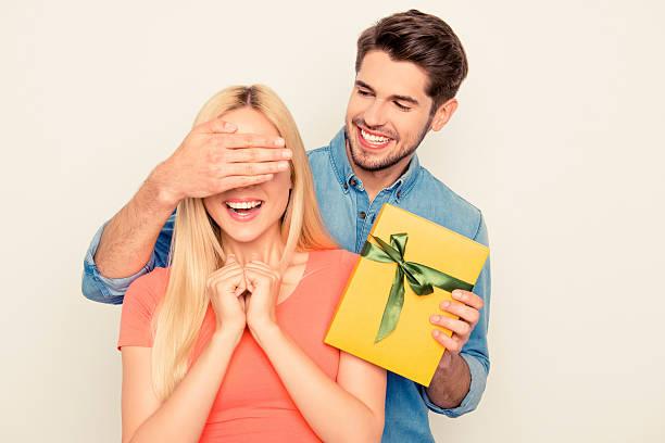 surprise! guy closing eyes of his girlfriend and holding present - jugendliche geburtstag geschenke stock-fotos und bilder