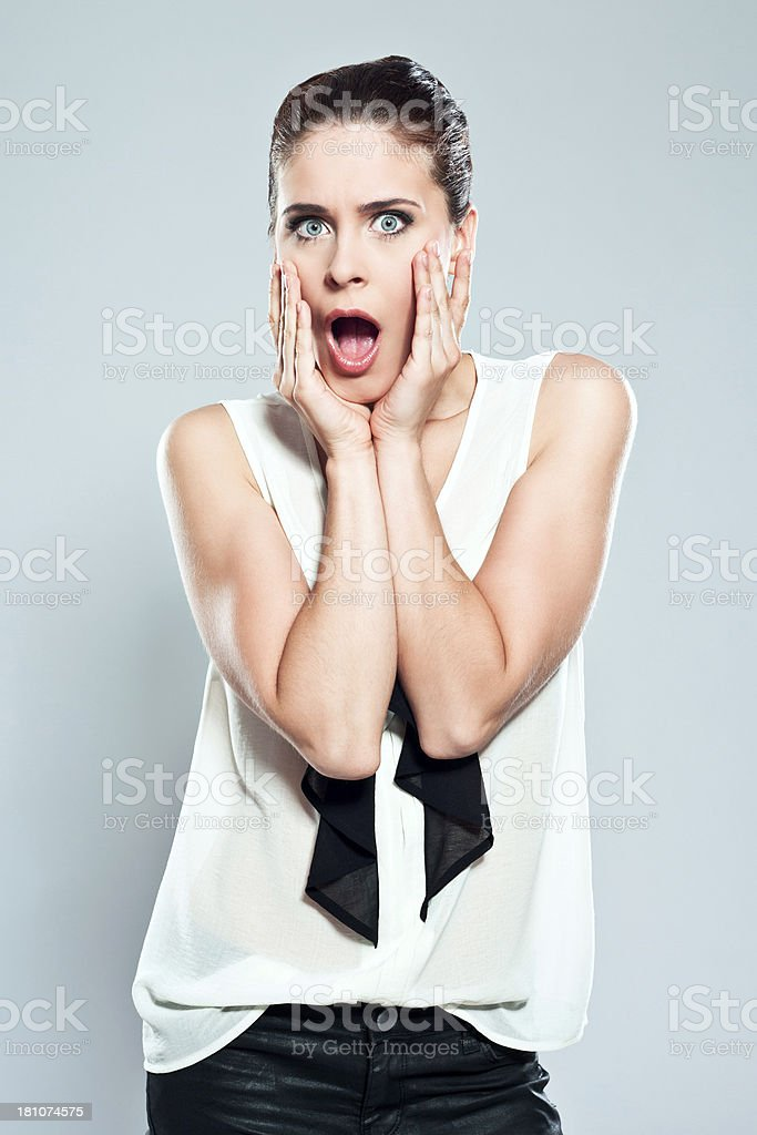 Surprise Portrait of surprised young woman staring at the camera with mouth open . Studio shot. 20-24 Years Stock Photo