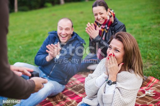 33 years old men is proposing his girlfriend while they are on picnic with friends