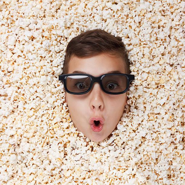 überrascht junge in stereoanlage brille suchen aus popcorn - niedlichen anime jungs stock-fotos und bilder
