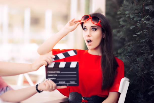 surprised actress with oversized sunglasses shooting movie scene - film oder fernsehvorführung stock-fotos und bilder