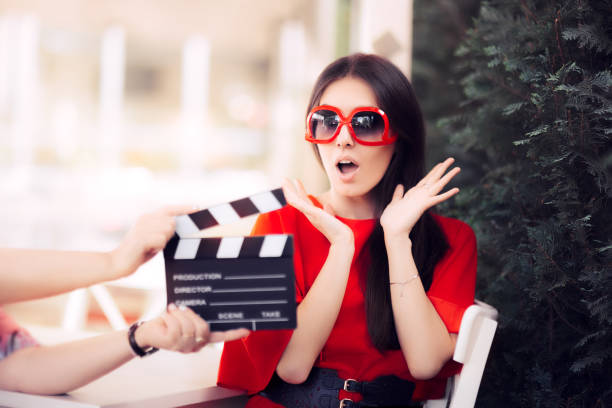 Surprised Actress with Oversized Sunglasses Shooting Movie Scene Diva in red dress and big shades starring in an artistic film diva human role stock pictures, royalty-free photos & images