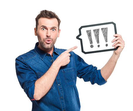 Surprised Adult Wearing Jeans Shirt Holding Speech Bubble In Hand Stock Photo - Download Image Now