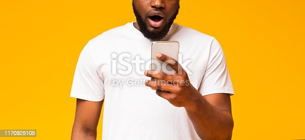 istock Surprised african american guy checking social networks on smartphone 1170925105