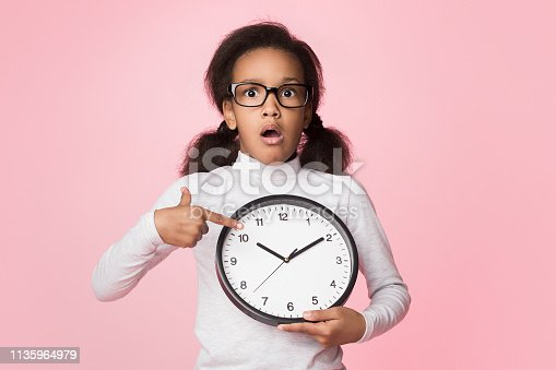 istock Surprised african-american girl holding big clock and pointing on it 1135964979