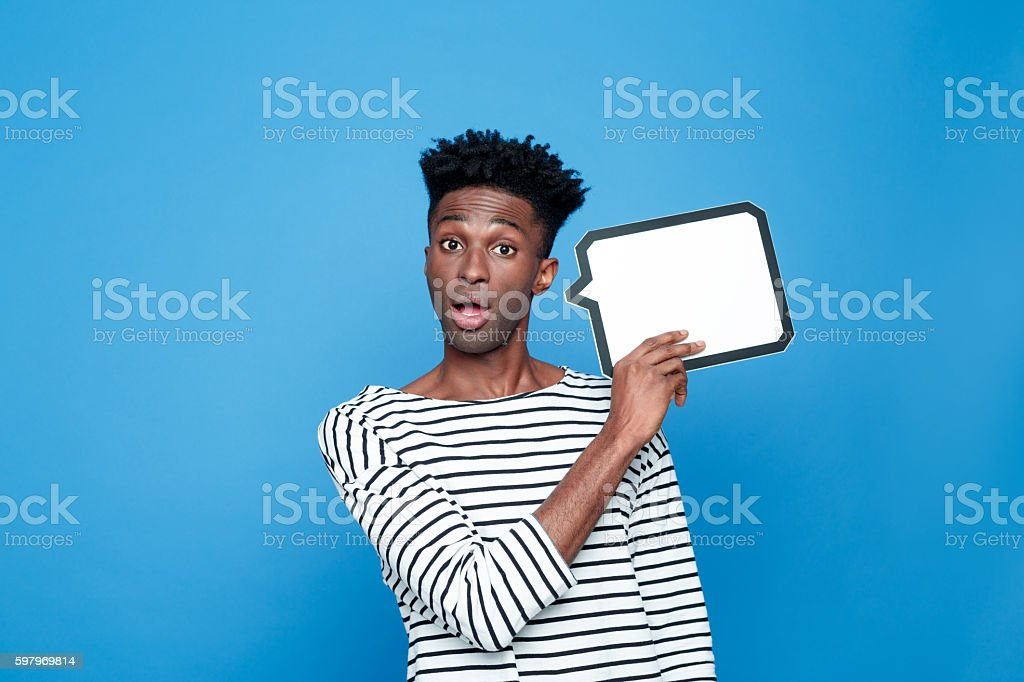 Surprised afro american guy holding speech bubble Portrait of surprised afro american young man wearing striped top, holding speech bubble in hand and looking at camera with mouth open. Studio portrait, blue background. Adult Stock Photo