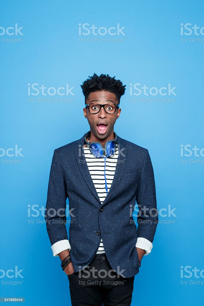 Surprised afro american guy in fashionable outfit Studio portrait of surprised afro american young man wearing striped top, navy blue jacket, nerd glasses and headphone, staring at camera with mouth open, rolling eyes. Studio portrait, blue background. Adult Stock Photo