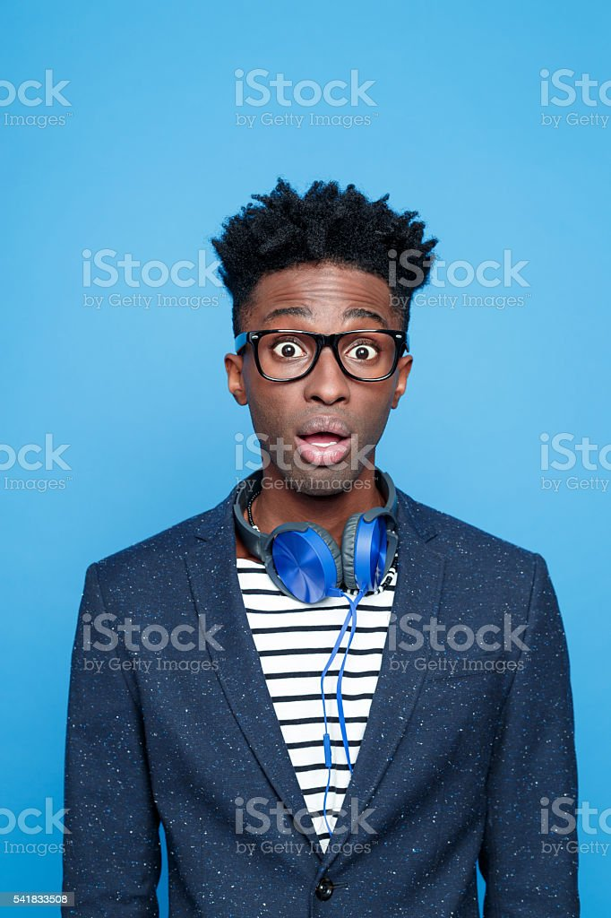 Surprised afro american guy in fashionable outfit Studio portrait of surprised afro american young man wearing striped top, navy blue jacket, nerd glasses and headphone, staring at camera, rolling eyes. Studio portrait, blue background. Adult Stock Photo