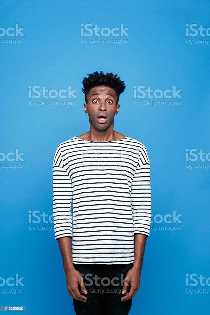 Surprised afro american guy Portrait of surprised afro american young man wearing striped top, staring at camera with mouth open, rolling eyes. Studio portrait, blue background. Adult Stock Photo