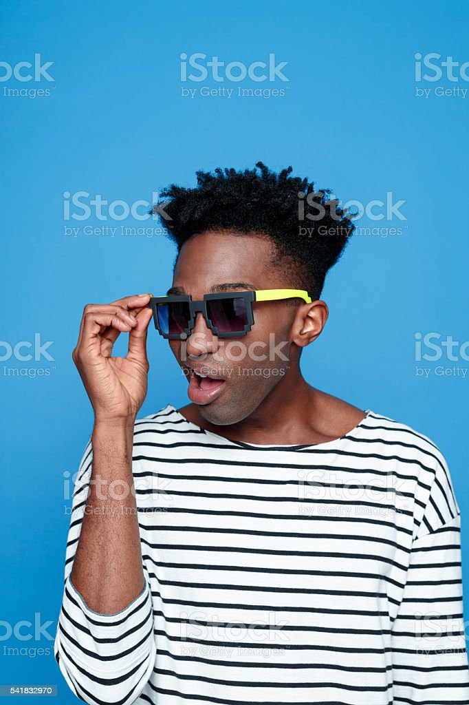Surprised afro american guy wearing sunglasses Surprised afro american young man wearing striped top and sunglasses. Studio portrait, blue background. Adult Stock Photo