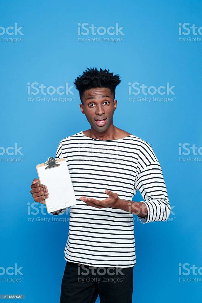 Surprised afro american holding clipboard Surprised afro american young man wearing striped top holding clipboard in hand. Studio portrait, blue background. Adult Stock Photo