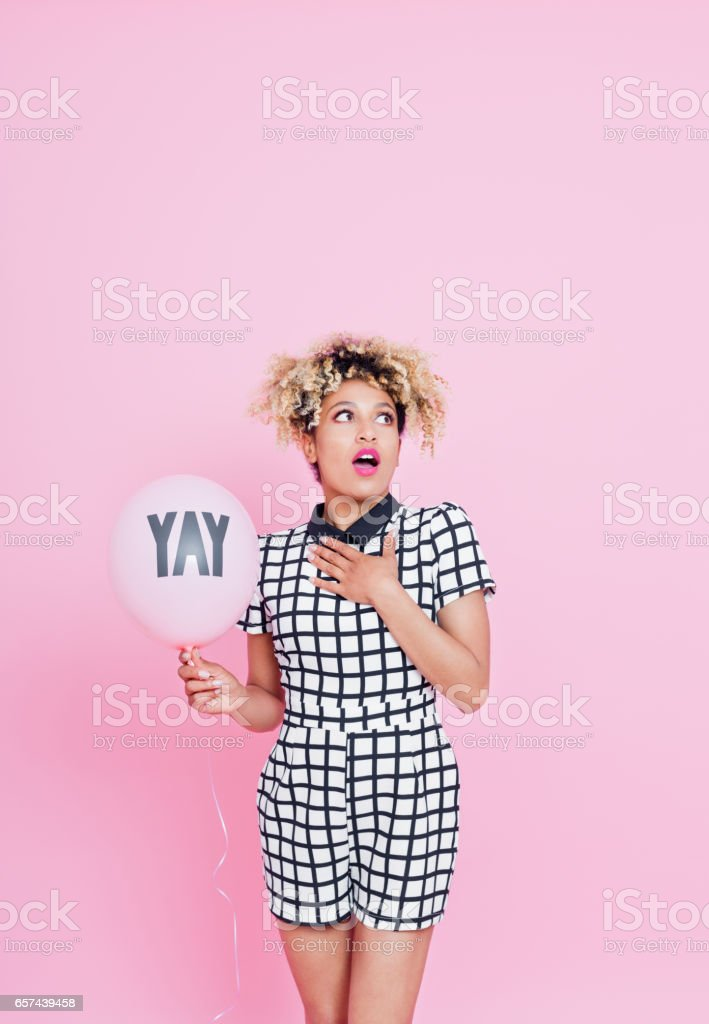 Surprised afro american woman holding pink balloon Studio portrait of surprised afro american young woman holding pink balloon with text YAY, looking away. Pink background. 20-24 Years Stock Photo