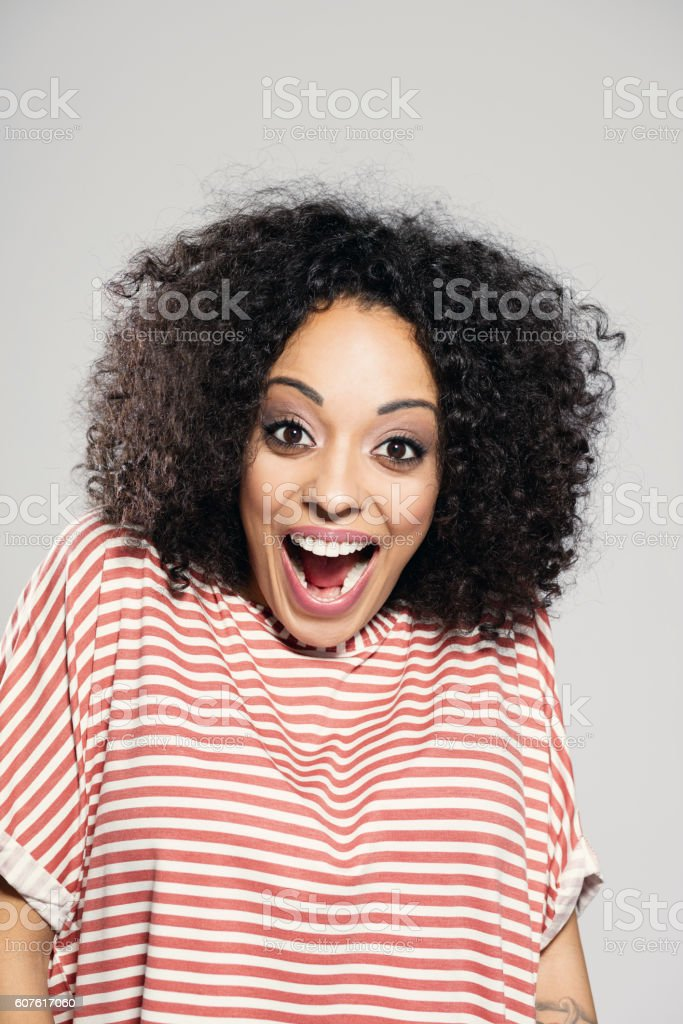 Surprised afro american woman laughing Portrait of surprised afro american young woman wearing striped top, standing against grey background and shouting at camera. Adult Stock Photo