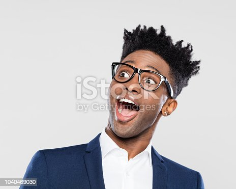 Studio portrait of surprised afro american young man in business suit and nerd glasses looking up with mouth open on white background.