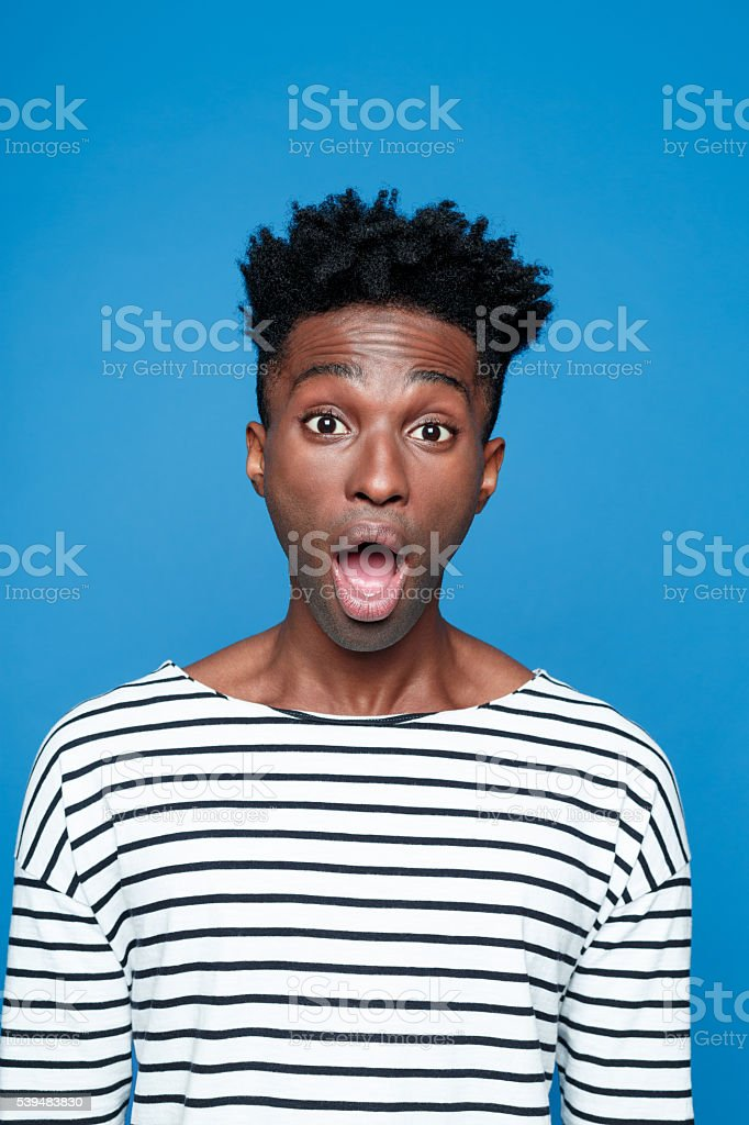 Surprised afro american young man Portrait of surprised afro american guy wearing striped long sleeved t-shirt, staring at camera with mouth open. Studio shot, blue background.  Adult Stock Photo